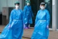 Health workers in protective gear outside an emergency entrance to a hospital in northern Spain. Photo: AFP