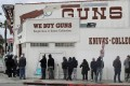 People wait in line outside to buy supplies at a US gun store. Photo: Reuters