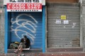 A homeless man sits in front of closed retail shops in Mong Kok on February 25, with Hong Kong in the grip of a Covid-19 outbreak. Photo: Edmond So