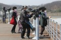 A family wearing face masks use binoculars to look across South Korea's border with the North at Imjingak in Paju last week. Photo: AP