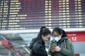 Chinese students stand in front of a departure board at Dresden Airport in Germany in March, as numerous flights are cancelled due to the coronavirus outbreak. Photo: dpa