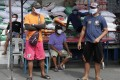 Men wearing protective masks stand near a village hall during the coronavirus lockdown in Manila on Friday. Photo: AP