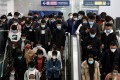 People wearing face masks crowd escalators inside a subway station during morning rush hour in Beijing, as workers across the country gradually return after weeks of lockdown and stay-at-home orders. Photo: Reuters