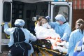 A woman arrives in an ambulance at a hospital in New York on Sunday. Photo: AFP