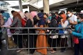 Commuters wearing face masks queue at a railway station in Jakarta on Monday. Photo: AFP