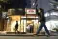 Pedestrians walk past an Oyo hotel in Tokyo. The start-up is placing thousands of employees on indefinite leave in a bid to survive the coronavirus pandemic. Photo: Bloomberg