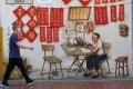 A man wearing a face mask walks past a mural in Chinatown in Singapore. The Chinese embassy has intensified its outreach campaign to citizens currently in the city state. Photo: AFP
