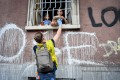 A volunteer distributes basic necessities to people during a lockdown in Milan, Italy. Photo: DPA