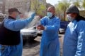 Volunteers spray disinfectant on each other as they deliver humanitarian aid to poor and large families Bishkek, Kyrgyzstan. The country has declared a state of emergency after the outbreak of Covid-19. Photo: EPA-EFE