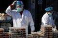 Workers prepare food orders outside a restaurant only offering takeaway business in Beijing. Photo: AP