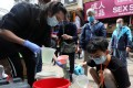Members of a charity group give away bleach to residents of Sham Shui Po on March 5, amid a Covid-19 outbreak in Hong Kong. Photo: Xiaomei Chen