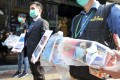 Hong Kong customs officers display the tainted face masks seized during a routine inspection. Photo: Nora Tam