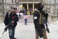Protesters carry rifles near the steps of the Michigan State Capitol building in Lansing, Michigan, on Wednesday. Photo: AP