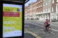 A cyclist passes by a bus stop with a public health warning on Covid-19 in Dublin on April 17, 2020. Photo: EPA-EFE
