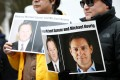 People hold signs calling for China to release Canadian detainees Michael Spavor and Michael Kovrig. Photo: Reuters