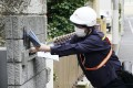 A postal worker delivers free cloth masks to a house in Tokyo on Friday under the controversial government programme. Photo: Kyodo
