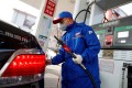 A pump attendant wears a mask as he refuels a car at a Sinopec gas station in China. The price of oil has plunged amid the coronavirus outbreak. Photo: Reuters
