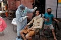 A doctor collects a swab sample from a man in India's Mumbai. Photo: Reuters