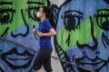 A woman wears a face mask she jogs along a cargo dock in Hong Kong. Photo: AFP