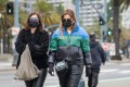 Pedestrians wearing protective masks walk on the Embarcadero in San Francisco, California, US, on Monday, April 20, 2020. Photo: Bloomberg