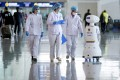 Medical workers look at a police robot at Wuhan Tianhe International Airport after travel restrictions on Wuhan, the epicentre of the Covid-19 pandemic, were lifted, on April 8, 2020. Photo: Reuters