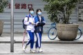 Students wear protective face masks while walking in Guangzhou, the capital of Guangdong, on Wednesday. Some schools in the city have started to resume. Photo: EPA-EFE