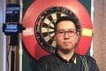 Kevin Leung Kai-fun in front of the dartboard and camera set up he uses in his Jordan flat for the PDC Home Tour series. Photo: Handout