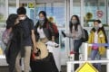 Travellers wearing face masks arrive at Vancouver International Airport in Richmond on April 20. Photo: Xinhua