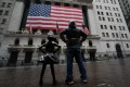 A man stands with the Fearless Girl statue across from the New York Stock Exchange on Wednesday. Photo: dpa