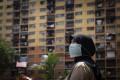 A woman walks near government apartments in downtown Kuala Lumpur, Malaysia, on April 30. Photo: AP
