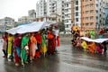 Bangladeshi garment workers shelter from the rain under a banner as they protest to demand their due wages, during a coronavirus lockdown in Dhaka on April 15. Photo: Reuters