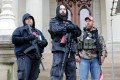 Armed protesters provide 'security' on the steps of the Michigan State Capitol in Lansing, demanding the reopening of businesses. Photo: AFP