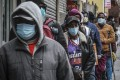 New Yorkers queue for distribution of masks and food. Photo: AP