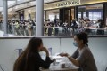 Diners enjoy lunch as protesters chant slogans in the IFC Mall. Photo: Bloomberg