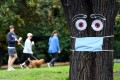 People walk past a mask and eyes stapled to a tree in Melbourne on April 20. While governments are being faulted for not preparing adequately for a pandemic, despite warnings, the climate change crisis is hiding in plain sight. Photo: AFP