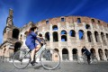 Women ride a bicycle past the Colosseum monument in Rome. Photo: AFP