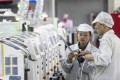 File photo of people working on machines at the Foxconn factory in Guiyang, China. Foxconn produces electronic devices for Apple and other leading IT companies. Photo: EPA-EFE