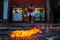 Customers cautiously exit a store in Hong Kong, as a Molotov cocktail burns on the street during a clash between protesters and riot police on November 2, 2019. Photo: Reuters