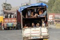 A truck carrying migrant workers leaves for Uttar Pradesh state from the outskirts of Mumbai on Thursday. Photo: AP