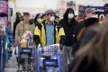 People wearing masks and gloves queue at a Walmart checkout in Uniondale, New York. By one estimate, the trade war has cost the average family in the US about US$460 a year. Photo: AFP