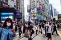 Pedestrians in Hong Kong don surgical masks amid the coronavirus pandemic. Photo: AFP