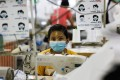 A worker wearing a face mask sews disposable surgical gowns for health workers at a garment factory in Yangon, Myanmar. Photo: AFP