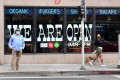 Pedestrians in front of a Los Angeles restaurant that is open for takeout only. California Governor Gavin Newsom announced guidelines for reopening that include self-distancing and stricter cleanliness procedures. Photo: AFP