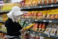 A customer wearing a protective mask and gloves at a supermarket in Seoul, South Korea. Photo: Bloomberg