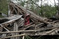 Family members stand among the debris of their destroyed home after Cyclone Amphan made landfall near the Bay of Bengal in India. Photo: EPA