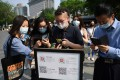 People wear face masks as a preventive measure against the Covid-19 coronavirus as they use a phone app to scan a code required to prove their health and travel status before being allowed to enter a shopping mall, in Beijing on May 2. Photo: AFP