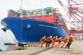 Workers wearing face masks rope a container ship at a port in Qingdao, Shandong province, China, on February 11. Global trade declined by 3 per cent in value during the first quarter of this year. Photo: China Daily via Reuters