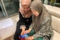 Aisya Amira Abam Malik teaches her grandmother how to use internet banking applications to send virtual green packets during Hari Raya. Many of Singapore's elderly citizens who are not digitally savvy have felt cut off during the Covid-19 restrictions. Photo: Kimberly Lim
