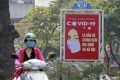 A motorcyclist drives past a Covid-19 poster in Hanoi. Photo: AP