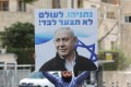 A supporter of Israeli Prime Minister Benjamin Netanyahu holds a sign that reads: 'Netanyahu will never walk alone!' Photo: EPA